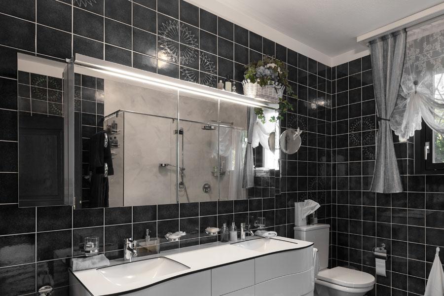 Kakelväggar med svart kakel i badrum