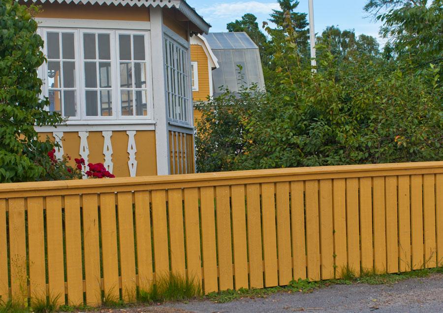 Villastaket målat med gul slamfärg.