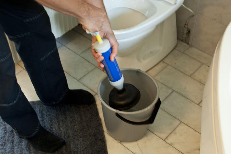Använder avloppspump för att rensa bort stopp i toalett