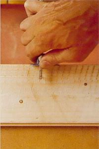 Lägg strykmåttets kloss stadigt mot brädans långsida.