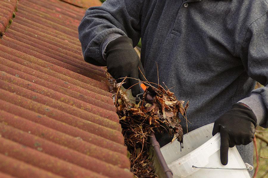 Rensar bort skräp och löv i hängrännor