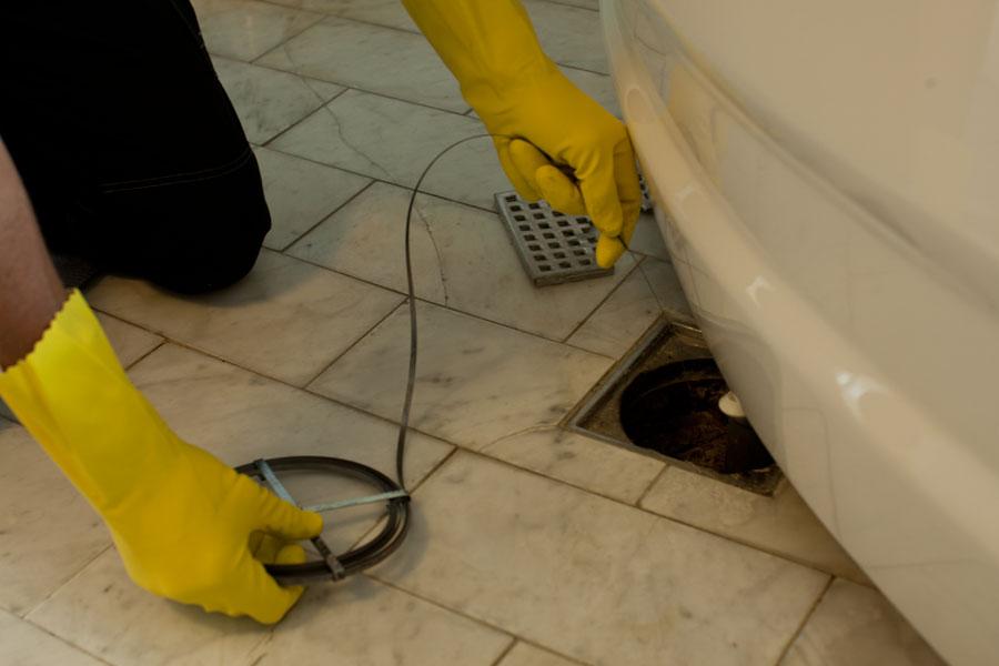 Rensar bort stopp med rensband i golvbrunn