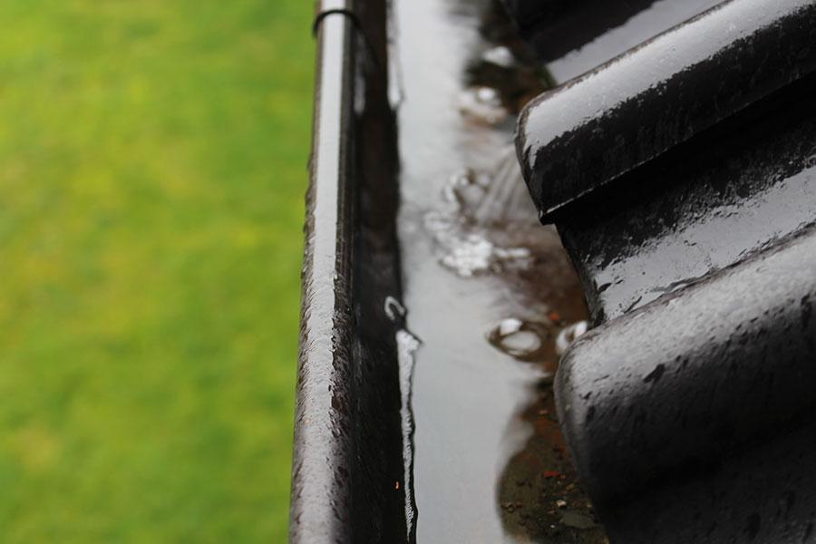 Stående regnvatten i hängränna med dåligt fall