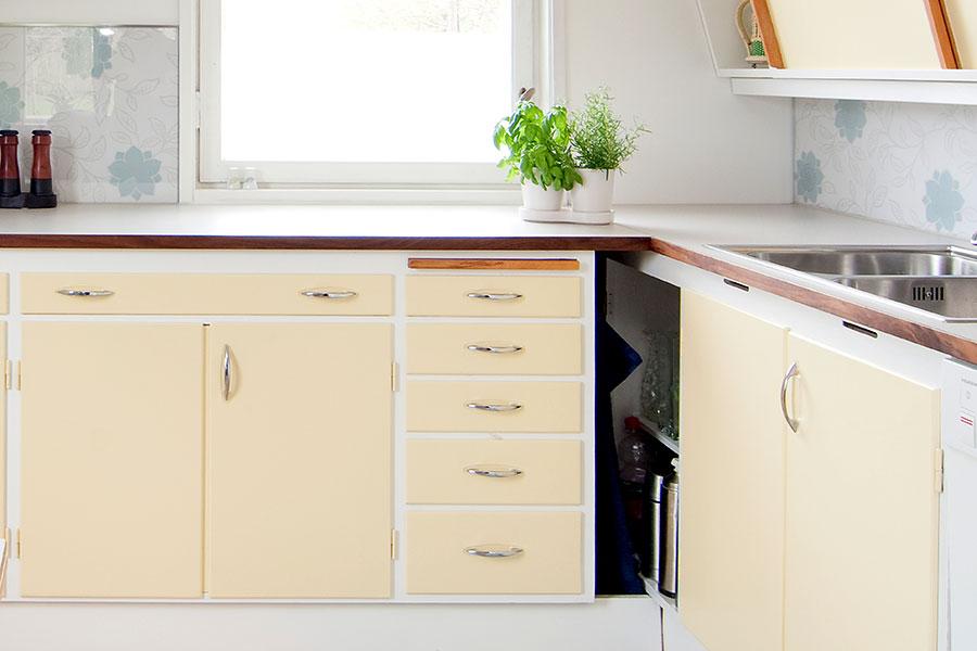 Synliga gångjärn på äldre köksinredning med kökshandtag i 50-tals stil