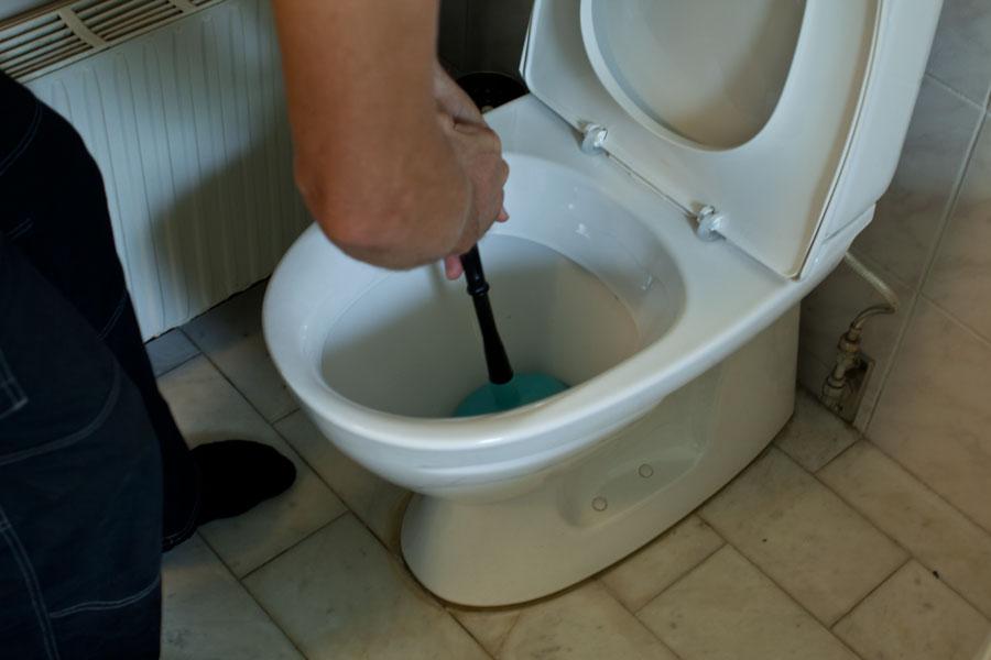 Trycker med vaskrensare för att få bort stopp i toalettstol