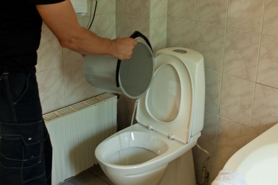Häller ned vatten i toalettstol för att få bort stopp
