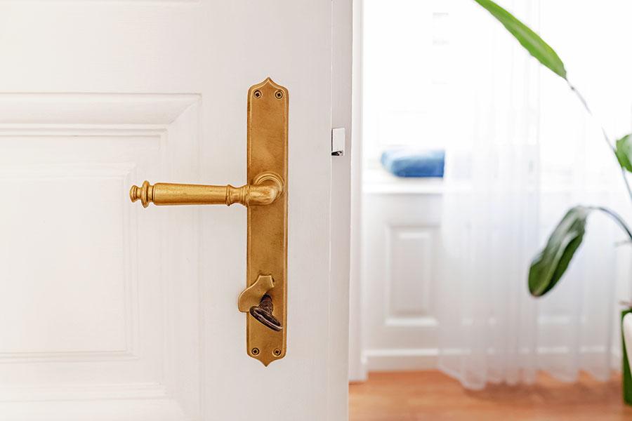 Äldre dörrhandtag och dörrtrycke på innerdörr