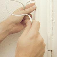 Lägg sladden under dörrfodret