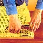Använder en häftpistol och fäst rottingen mot ramen med klammer