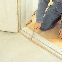 Lossa dörrfodret och skruvar som håller tröskeln mot golvet