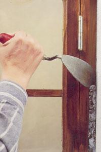 Ta bort allt löst bruk och andra materialrester mellan vägg och fönster.