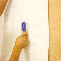 Använd saxskänkeln och tryck ner tapeten runt dörr eller fönsterfoder