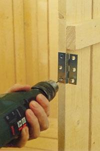 Förborra hål för gångjärnet i väggen.
