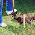 Schaktar bort jord med spade