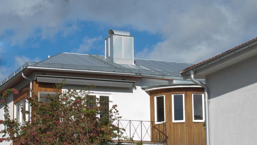 Vallmat tak i silverfärgad bandplåt. Skorstensintäckning och skorstenshuv är inklädda i machande färg.