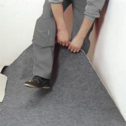 Lyfter upp hörnet på mattan och sparkar in den i hörnet