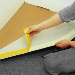 Drar bort skyddspapper från tejpen på heltäckningsmattans undersida