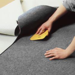 Pressar ut bubblor och veck i mattan med en spackelspade av plast