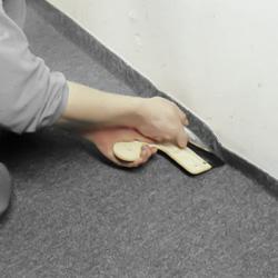 Trycker med spackel mot väggen och skär med mattkniv