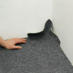 Kontrollerar så att heltäckningsmattan ligger tätt mot väggen och hörn
