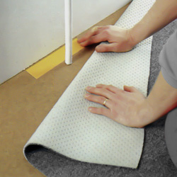 Sätter fast dubbelhäftande tejp mellan rör och vägg