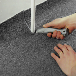 Gör snitt på heltäckningsmattan på varje sida av röret