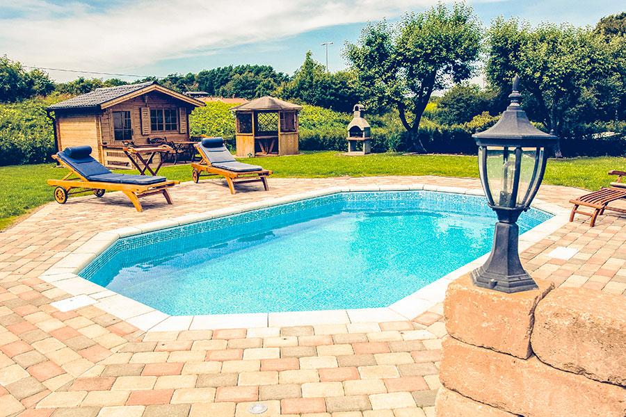 Pool för trädgården som är nedgrävd i marken men snygg marksten och kantsten runt poolkanten