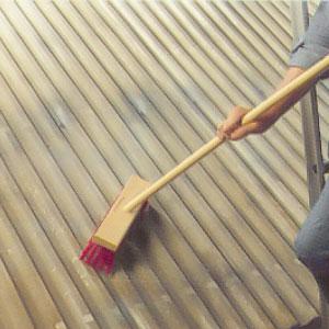 Sopar bort all lös smuts och skräp från taket med en styv borste