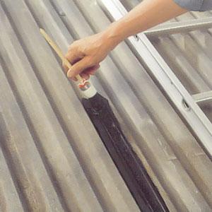 Använder en rund anstrykare och täckmålar kanter, hörn och falsar på plåttaket