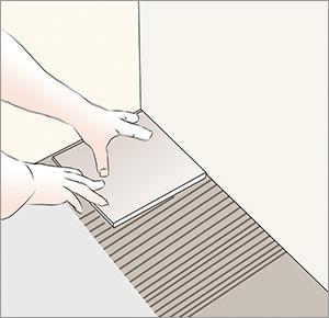 lägger första klinkerplattan i ett hörn