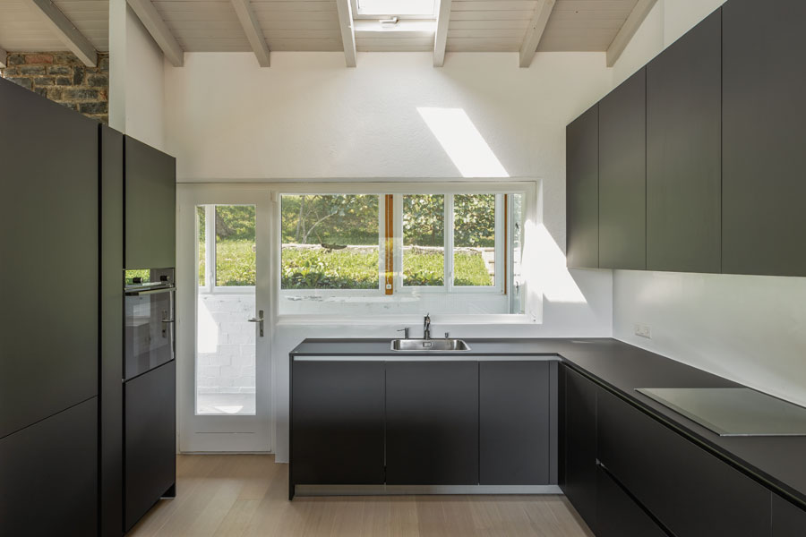 Svart kök med mattsvarta skåp och köksluckor