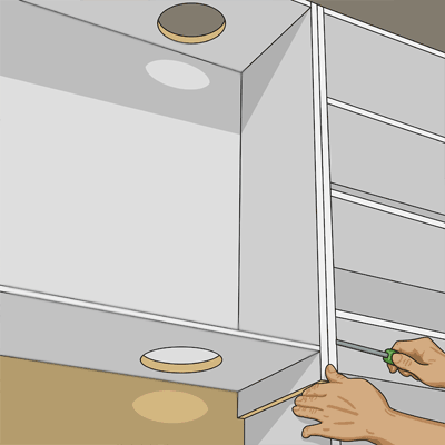 Sätter skåpet för köksfläkten på plats
