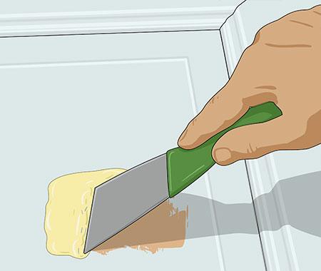 Skrapar loss färgen på dörren med en spackelspade