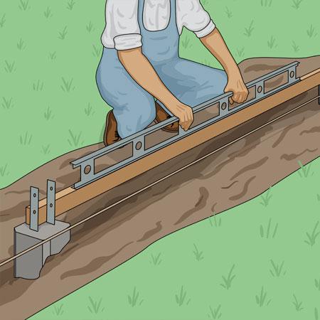 kontrollerar betongplintar för staketstolpar med vattenpass