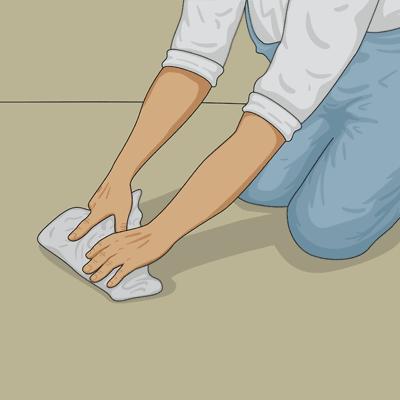 Pressar fast mattan med en spackelspade inlindad i en trasa