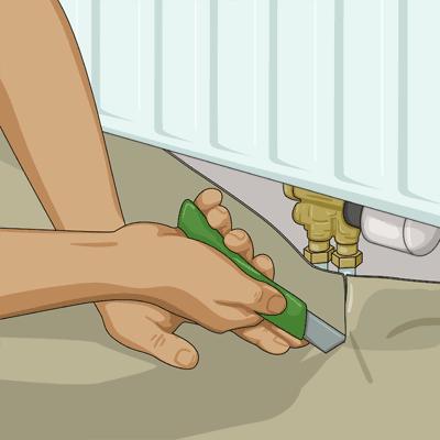 Trycker plastmattan mot rörledningarna. Skär med den raka kniven